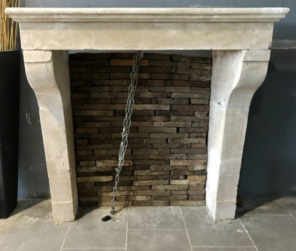 antique limestone fireplace in our showroom at Caen