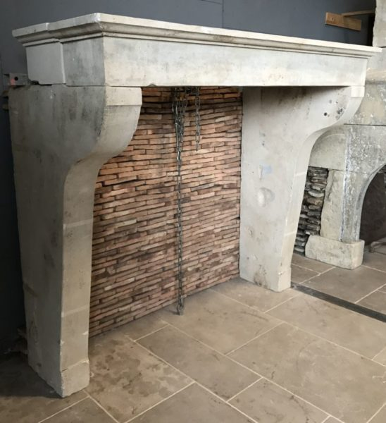 antique french limestone fireplace in our showroom