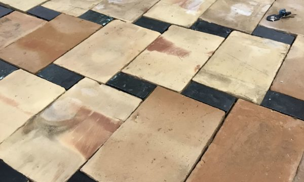 salvaged terracotta tiles with black rectangle floor tiles