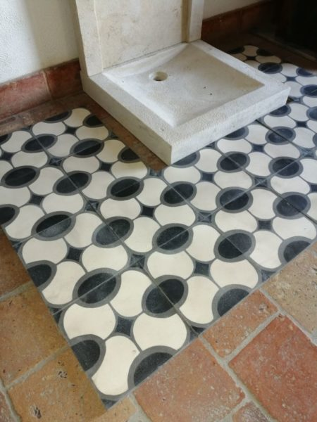 oval pattern with black, grey and beige cement tile