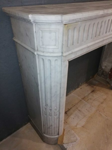 zoom on the left side of the white marble mantel